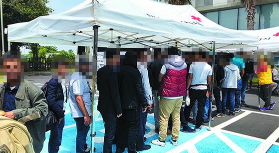 지난달 18일 제주 출입국·외국인청 앞마당에 마련된 대한적십자사 의료봉사 부스에 몰린 예멘 난민 신청자. 건강검진 차례를 기다리고 있다. [최충일 기자]