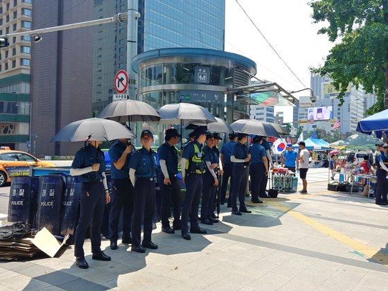검은 우산과 팔토시로 햇빛을 피하고 있는 의경들. 김정연 기자