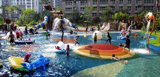 전국 대부분 지역에 폭염 특보가 내려진 21일수영장으로 변한 대전 도심 한 아파트 놀이터에서 아이들이 물놀이하며 더위를 식히고 있다. [연합뉴스]