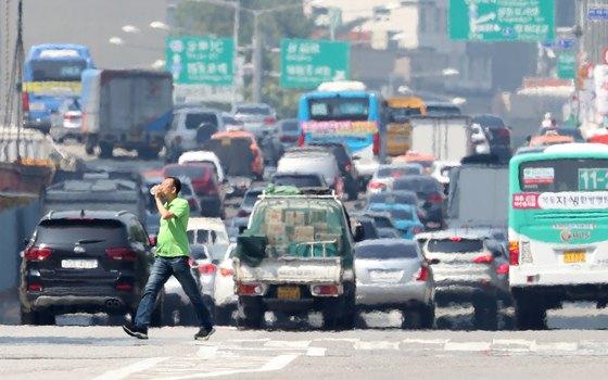 서울의 낮 최고기온이 36도까지 오르는 등 기록적인 폭염이 계속되는 21일 서울 여의대로 횡단보도에서 한 시민이 물을 마시며 발걸음을 옮기고 있다. [뉴스1]