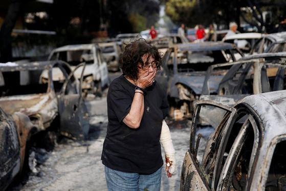 아테네 북동부 해안도시 마티에서 화마에 타버린 자동차를 한 주민이 바라보고 있다. [로이터=연합뉴스]