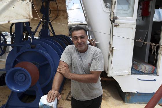 참혹한 그리스 아테네 화재 현장에도 이름없는 한 의인의 미담이 전해져 감동을 더했다. 라피나 해안에서 화마를 피해 극적으로 탈출한 생존자들을 구한 이집트 어부 Halil Tawefik가 25일 아테네 라피나 항구에서 낚시 보트를 탄 채 포즈를 취하고 있다. [ AP =연합뉴스]