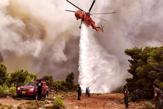 소방헬기가 24일 아테네 키네타 지역 에서 화재 진압을 하고 있다. [AFP=연합뉴스]