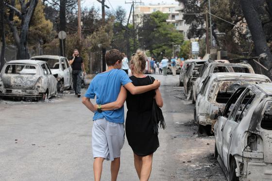 24일 아테네 마티지역 화재 현장에서 생존한 한 가족이 잔해 속을 걷고 있다. [EPA=연합뉴스]