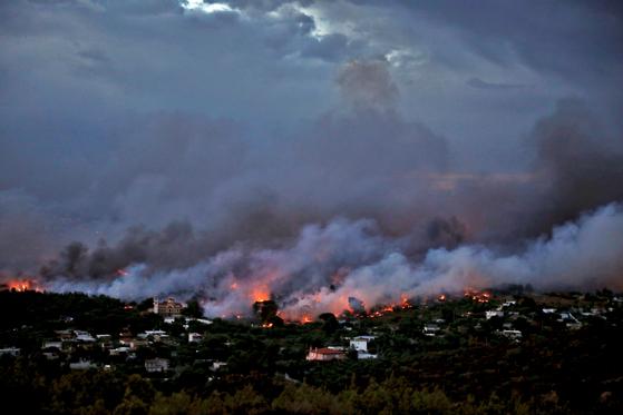 24일 아테네 라피나 지역 주택들이 불타고 있다. [ REUTERS=연합뉴스]