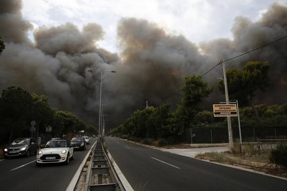 23일 아테네 북동쪽 교외 네오 보츠사 지역 도로가 통제 불능 상태에 빠진 채 연기로 뒤덮혀있다. [EPA=연합뉴스]