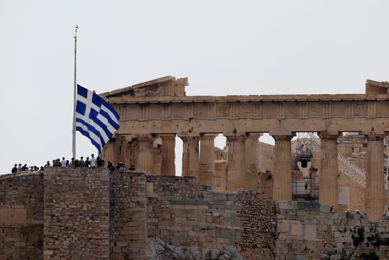 25일 그리스 아테네 파르테논 신전 인근에 그리스 국기가 조기로 게양되어 있다. [REUTER=연합뉴스]