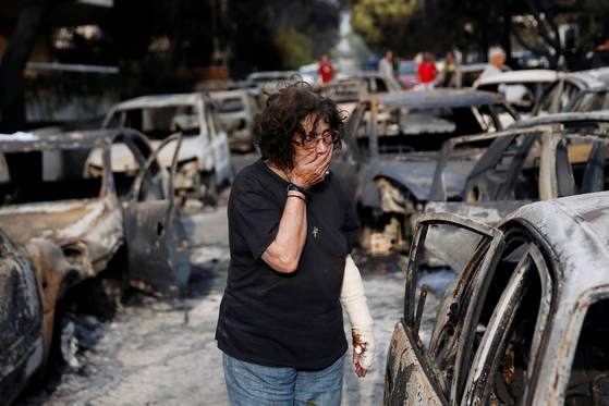 24일 아테네 마티에서 화재 생존자가 화재로 소실된 잔해속에서 망연자실하고 있다. [ REUTER=연합뉴스]
