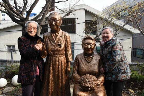 전쟁과여성인권박물관 정원에는 평화비를 만든 김서경·김운성 조각가의 '김복동 길원옥은 평화다'가 있다. 사진은 김복동(왼쪽)·길원옥 할머니가 각자 자신의 조각과 함께한 모습.