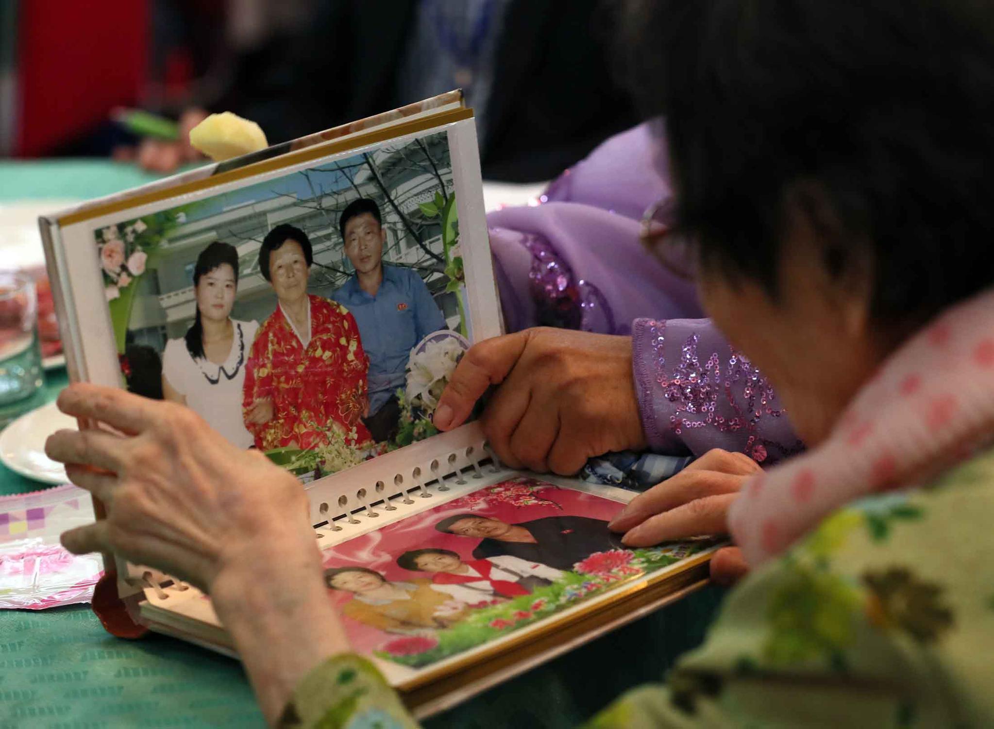 제21차 이산가족 상봉행사 1회차 첫날인 20일 오후 금강산호텔에서 열린 단체상봉에서 한신자(99)할머니가 북측의 딸들 김경실(72), 김경영(71)의 사진을 살펴보고 있다. [뉴스통신취재단]