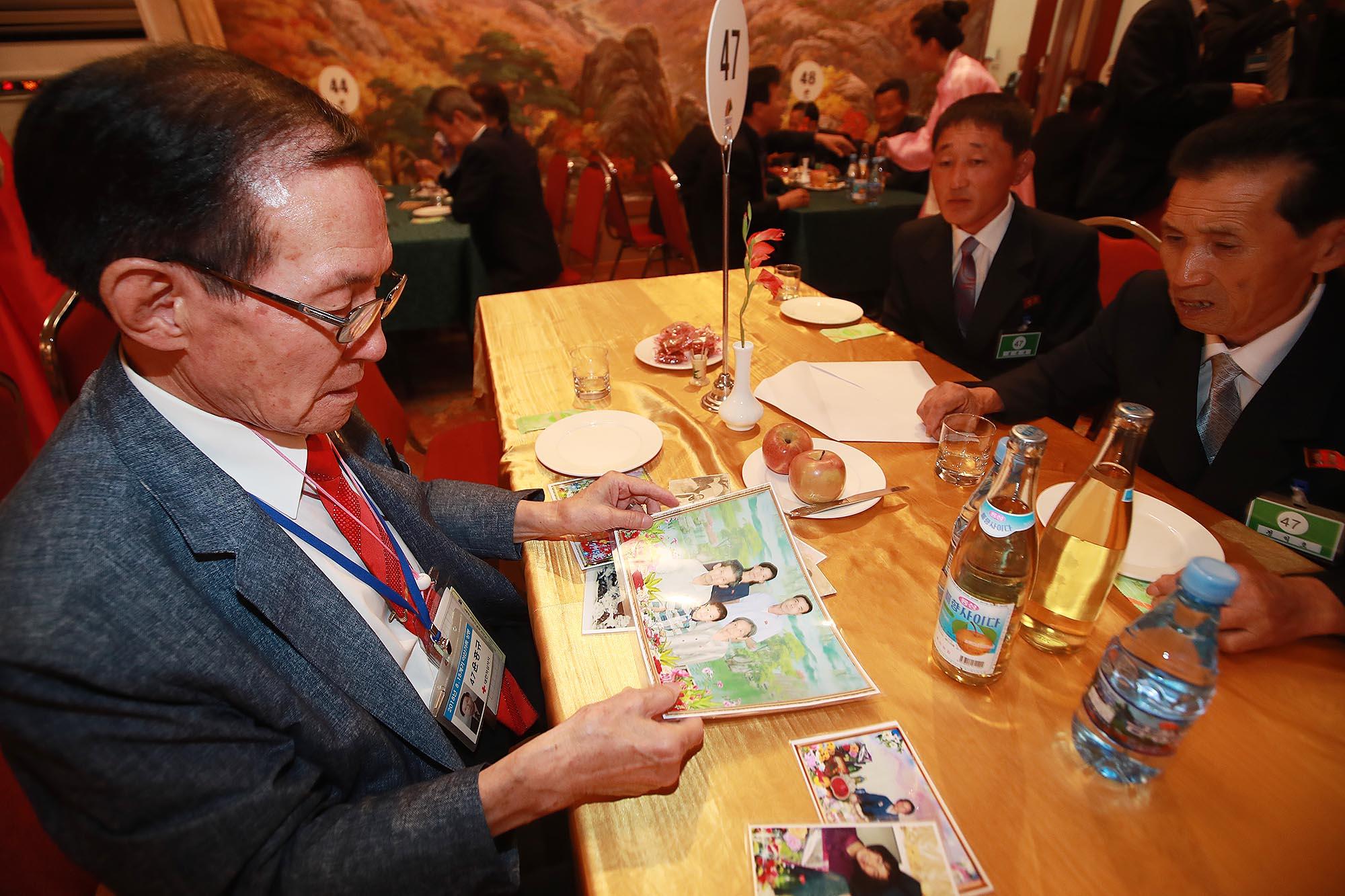 남측 윤흥규(92) 할아버지가 북측에서 온 외조카손자 김상욱(38)씨의 가족사진을 보고 있다.사진공동취재단
