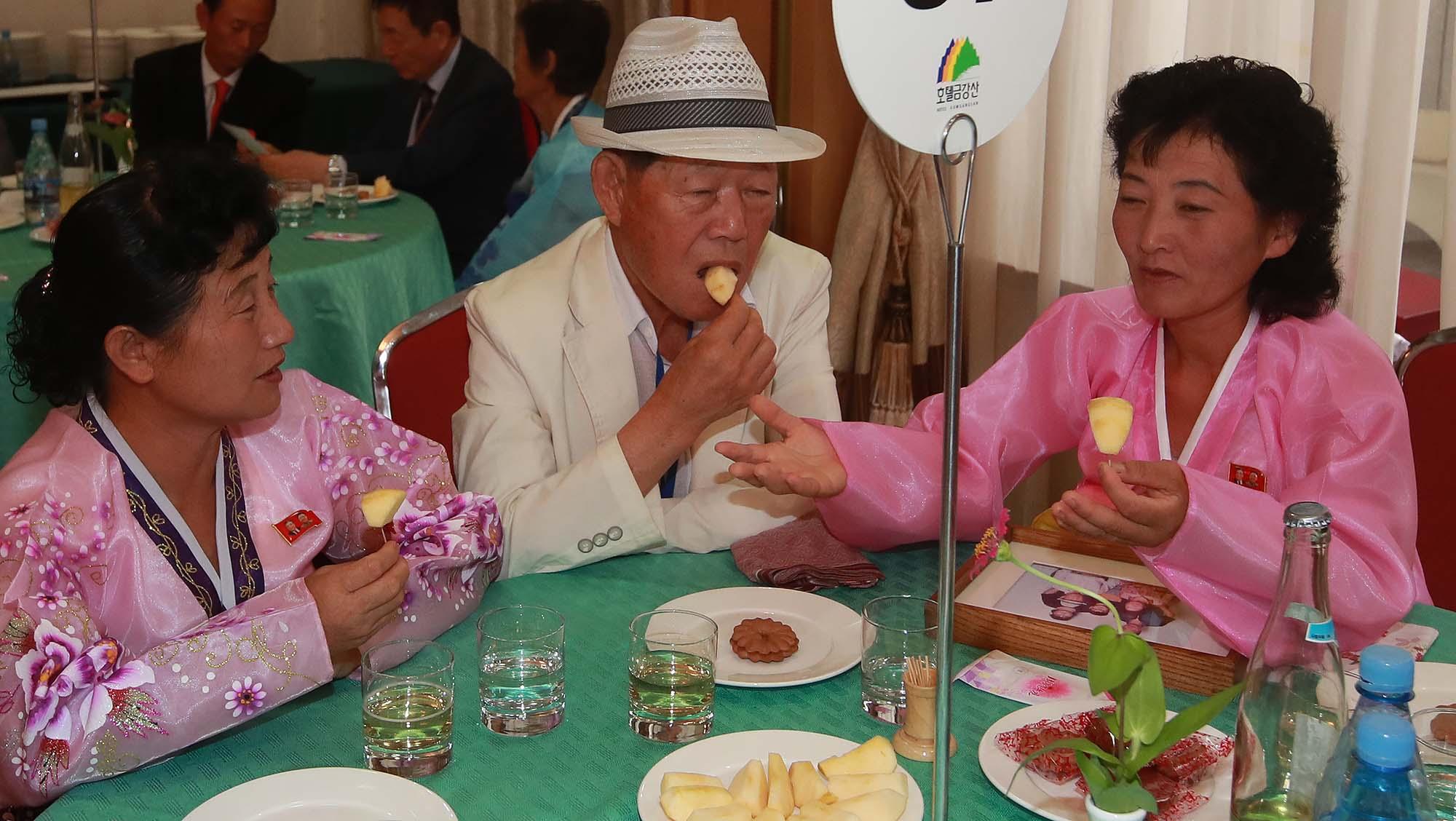 20일 오후 고성 금강산면회소에서 열린 단체상봉에서 남측 최학진(80) 할아버지가 북측에서 온 조카 최용순, 최용복씨와 과일을 먹으며 이야기를 나누고 있다. 사진공동취재단