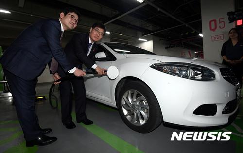전기차 충전 시연하는 조경규 환경부 장관-김종인 롯데마트 대표