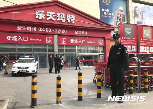 베이징 롯데마트 앞에 서있는 경찰관