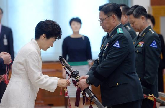 지난 2015년 9월 박근혜 전 대통령(왼쪽)이 청와대 충무실에서 열린 군 장성 및 보직 신고식에서 박찬주 제2작전 사령관에게 수치를 달아주고 있다. [청와대사진기자단]