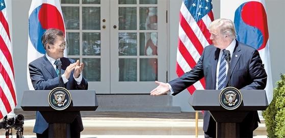 문재인 대통령이 6월 30일(현지시간) 백악관에서 공동 언론발표를 마친 후 박수를 치자 도널드 트럼프 미국 대통령이 악수를 청하고 있다. / 사진:청와대사진기자단