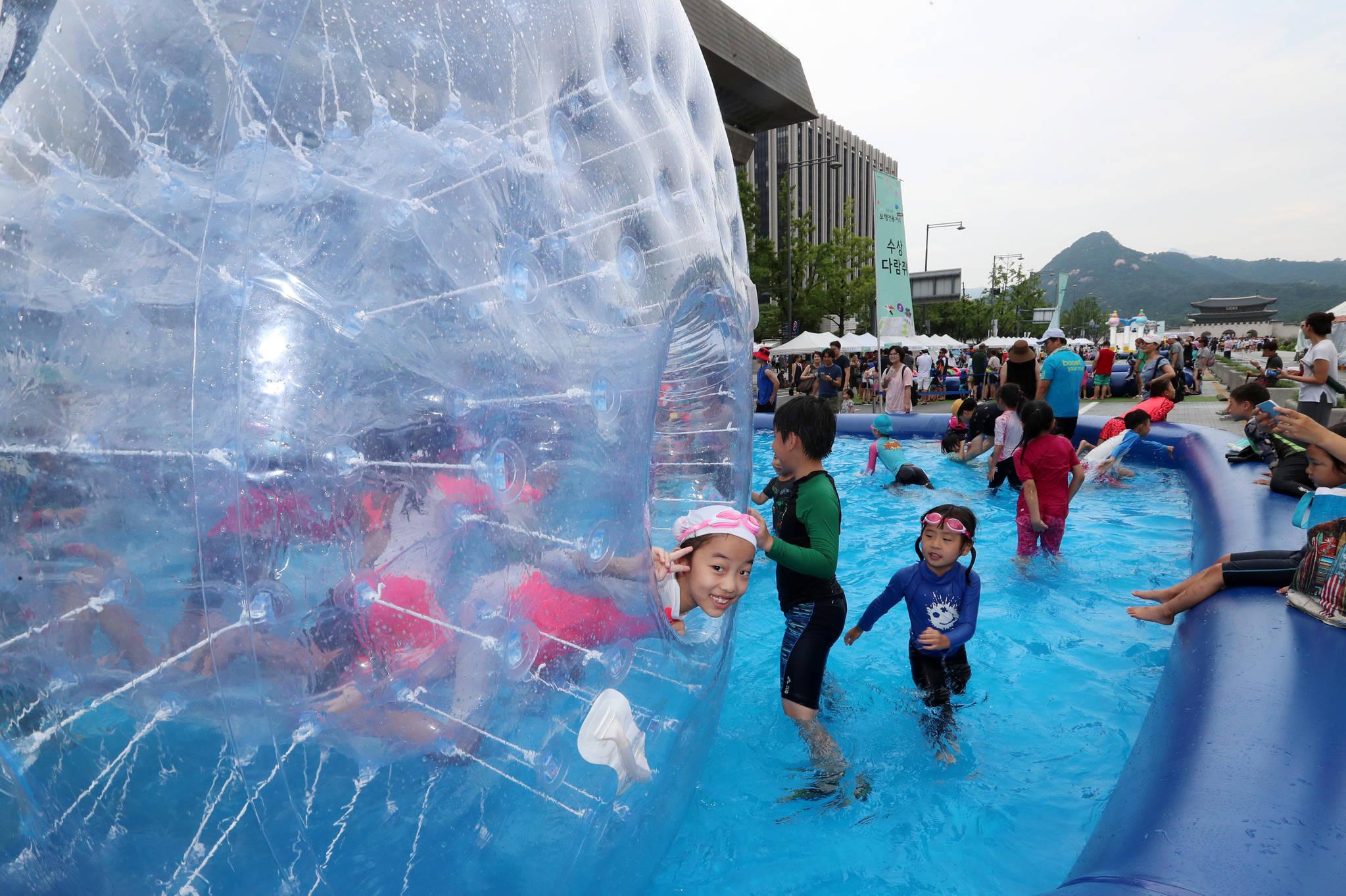 6일 서울 종로구 세종대로에서 열린 물놀이 페스티벌에 마련된 다람쥐통을 타며 어린이들이 물놀이를 즐기고 있다.조문규 기자