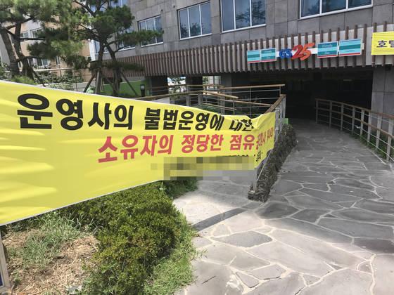 제주도 서귀포시 서귀동 G호텔 주차장에 '점유권을 행사 중'이라는 현수막이 달려 있다. 최충일 기자