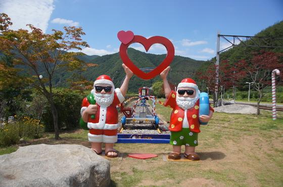분천역 한여름 산타마을에서 반바지를 입은 산타 모형이 레일바이크 앞에 있다. 백경서 기자