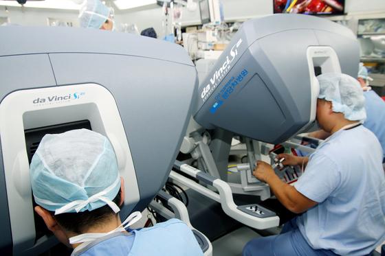 다빈치 로봇를 이용해 진료과가 다른 두 명의 의사가 동시에 수술하는 모습. 이러한 로봇 수술은 암 종류에 따라 건보 적용 여부가 갈릴 것으로 보인다. [중앙포토]