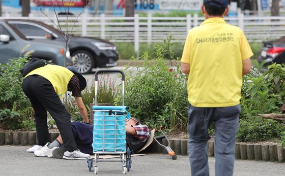 서울시 폭염 특별대책반 대원이 8일 서울역 광장에서 노숙인의 건강상태를 살피고 있다. 대책반은 노숙인들에게 생수와 식염 포도당을 나눠 준다. [우상조 기자]