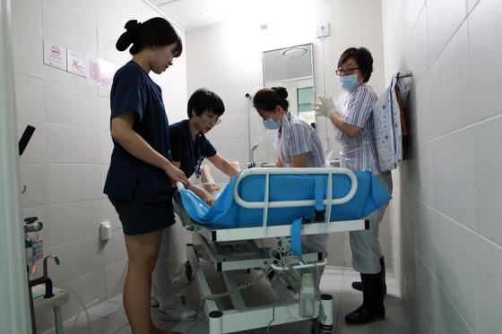 서울의 한 병원 간호사들이 간호간병통합서비스 병동에서 환자를 챙기고 있다. 정부는 간호간병통합서비스 적용 병상을 2022년까지 10만개로 늘린다는 목표다. [중앙포토]
