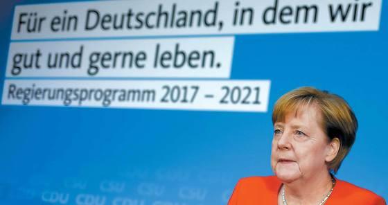 앙겔라 메르켈 총리가 지난 3일 베를린에서 완전고용 실현 등이 담긴 공약을 논의하고 있다. '잘살고, 살고 싶은 독일을 위하여'라는 슬로건이 걸려 있다. [AP=연합뉴스]