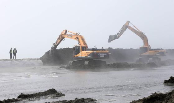 전북 김제시 새만금 동서2축 도로 건설 현장에 안개가 잔뜩 끼어 있다. 바다를 메워 군산시 새만금방조제까지 16.5km를 연결하는 공사에 투입된 굴착기들이 매립 작업을 하고 있다. [프리랜서 장정필]