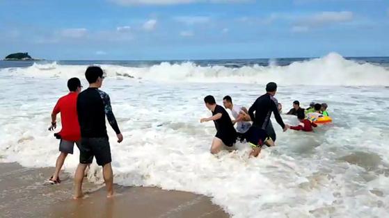 바다에 빠진 한 남성을 구하기 위해 피서객들이 인간띠를 만들고 있다.[고성=연합뉴스]