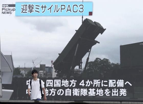 12일 일본 방위성이 패트리엇 미사일(PAC3)을 이동 배치했다는 뉴스가 나오는 도쿄 시내 대형 전광판 앞을 한 남성이 지나가고 있다. [도쿄 AP=연합뉴스]