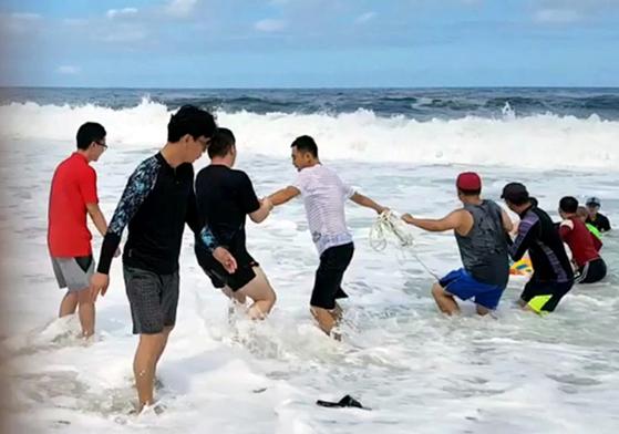 지난 12일 강원 고성군 토성면 봉포리 한 해변에서 바다에 빠진 40대 남성을 피서객들이 인간 띠를 만들어 구조하고 있다. [고성=연합뉴스]