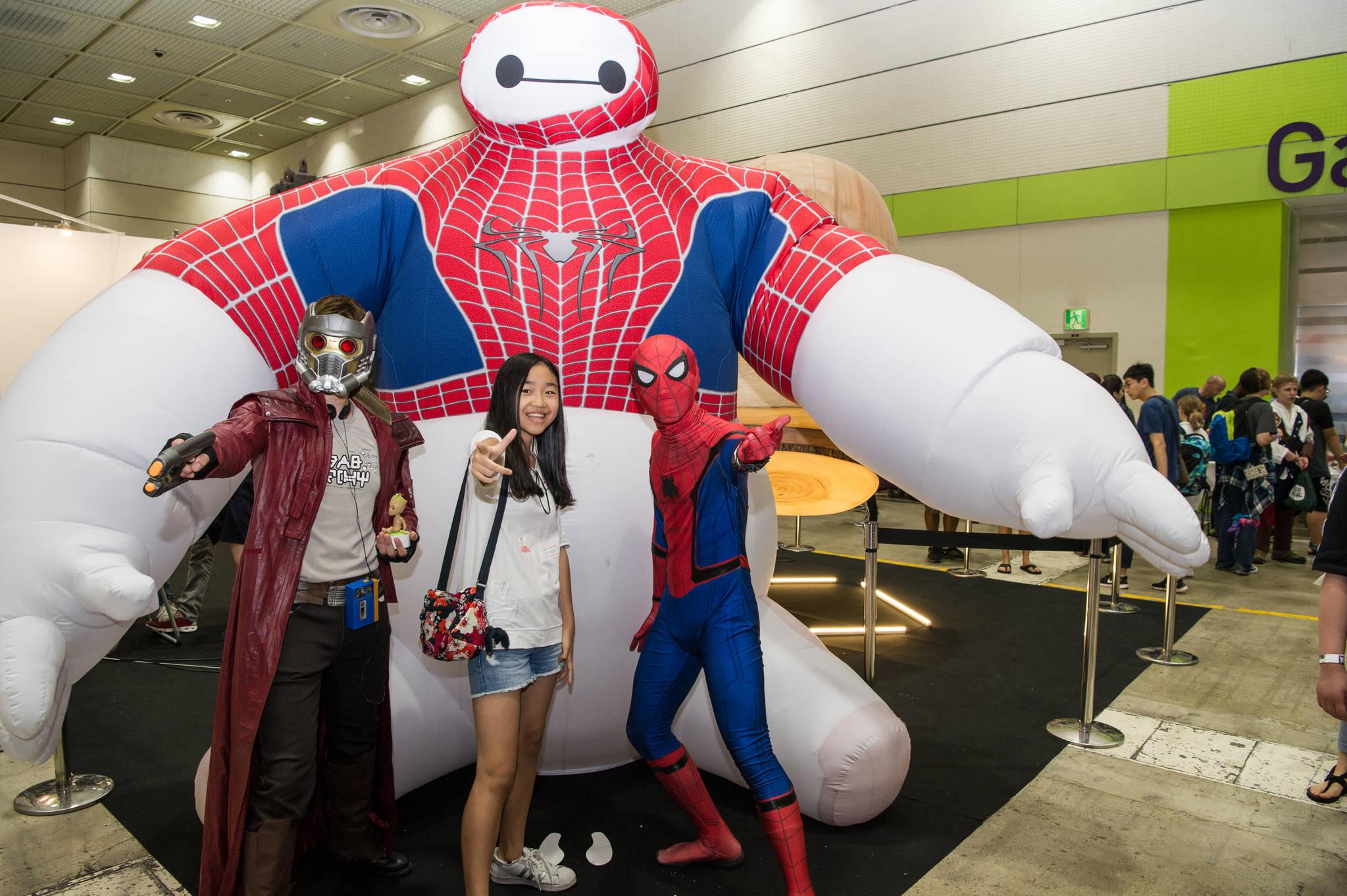 [어서 와, 코믹콘은 처음이지?] 코믹콘 서울을 찾은 여성 관람객이 전시장 입구에 설치된 대형 에어 피규어(Air Figure)를 배경으로 마블 수퍼 히어로로 변장한 코스튬 플레이어들과 사진을 촬영하고 있다.