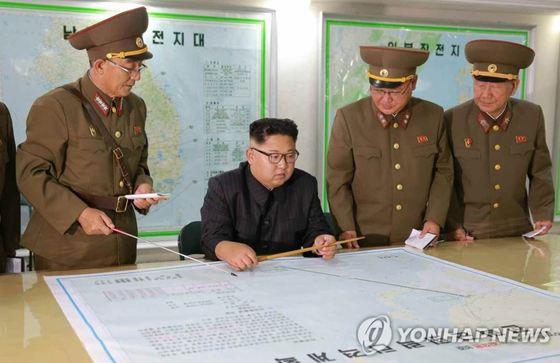 김정은 북한 노동당 위원장이 지난 14일 전략군사령부를 시찰하면서 김락겸 전략군사령관으로부터 '괌 포위사격' 방안에 대한 보고를 받았다고 노동신문이 15일 보도했다. [노동신문=연합뉴스]