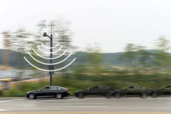 현대?기아차가 경기도 화성시에 구축한 '차량과 사물간 통신' 인프라. 교차로에 설치한 통신 안테나를 통해 교통신호 정보가 시험 차량에 전달되고 있다. [사진 현대차]
