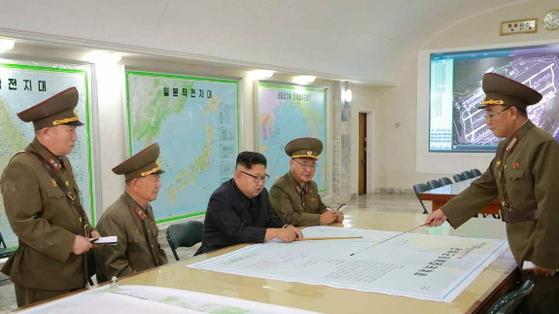 김정은 북한 노동당 위원장이 지난 14일 전략군사령부를 시찰하면서 김락겸 전략군사령관으로부터 '괌 포위사격' 방안에 대한 보고를 받았다고 노동신문이 15일 보도했다. [연합뉴스]
