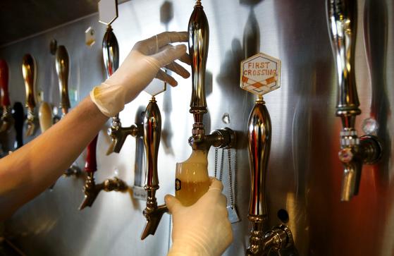 일본 맥주제조사 기린은 연내 제조공정에 인공지능(AI)를 도입할 방침이다. 사진은 2년 전 기린이 도쿄 시내에 문을 연 수제 맥주가게에서 생맥주를 담는 모습. [도쿄 AP=연합뉴스]