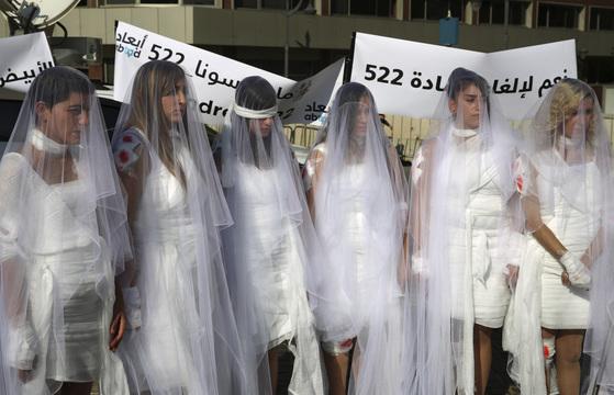 지난해 12월 피해자와 결혼한 성폭행범에게 면죄부를 주는 내용이 포함된 형법 522조 철폐를 요구하는 레바논 여성운동가들이 웨딩드레스를 입고 시위 중이다. 16일 레바논 의회는 이 법안을 폐지하기로 결정했다. [AP=연합뉴스]