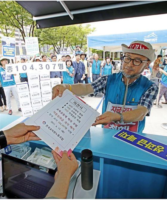 지난 6월 전교조 관계자 교원 성과급제 폐지에 찬성하는 교사 10만명의 서명을 받은 의견서를 국민인수위원회에 전달하고 있다. [연합뉴스]