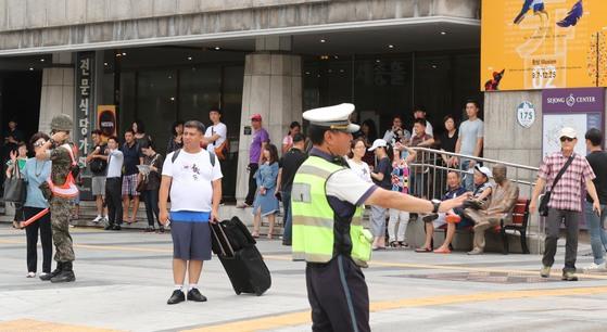 23일 오후 2시 민방위훈련이 시작되자 군인,경찰,공무원 등 통제요원들이 서울 광화문광장 인근에서 시민,외국인들에게 보행통제를 하고 있다. 최승식 기자