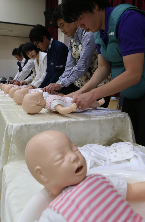 예비아빠 임산부 체험행사에서 기저기 갈기 연습을 하고 있다.[중앙포토]