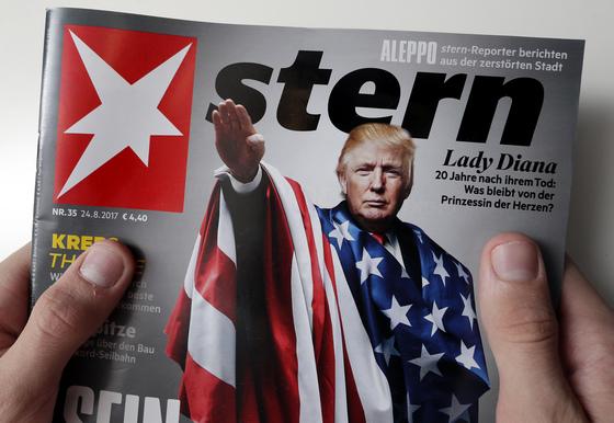 25일(현지시간) 독일 베를린에서 한 독자가도널드 트럼프 미국 대통령이 나치식 거수경례를 하는 합성 사진을 표지에 실은 시사 주간지 '슈테른(Stern)'을 들고 있다. [AP=연합뉴스]