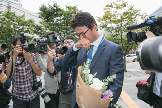 서울 마포구 YTN 사옥으로 출근하던 노종면 기자가 꽃다발을 받고 눈물을 훔치고 있다. [사진 YTN]