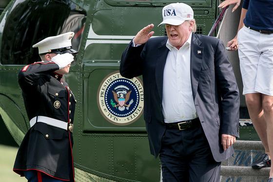 트럼프 미 대통령이 27일 백악관에 착륙한 전용 헬기에서 내리며 경례를 하고 있다. [EPA=연합뉴스]