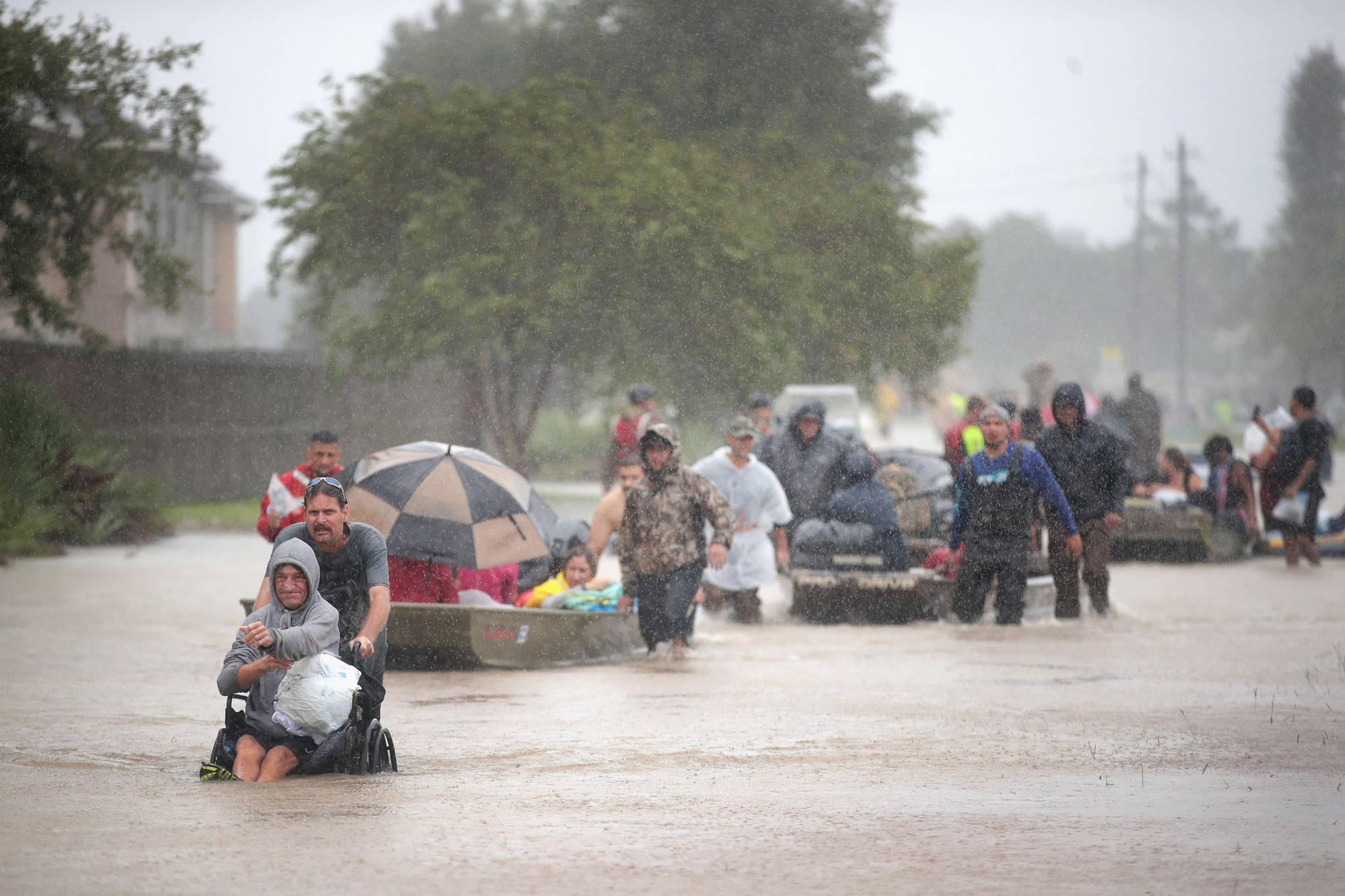 28일(현지시간) 미 텍사스 휴스턴 주민들이 허리케인 '하비'가 쏟아부은 비로 인해 물에 잠긴 도심을 줄지어 탈출하고 있다.[AFP=연합뉴스]