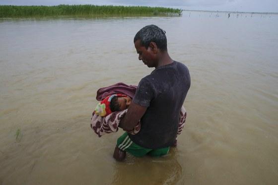 네팔 홍수로 폐렴을 앓다 숨진 8살 조카를 코시 강에 데려간 삼촌. 마른 땅이 남아 있지 않아 묻을 곳이 없어 강물 장례를 치렀다. [EPA=연합뉴스]