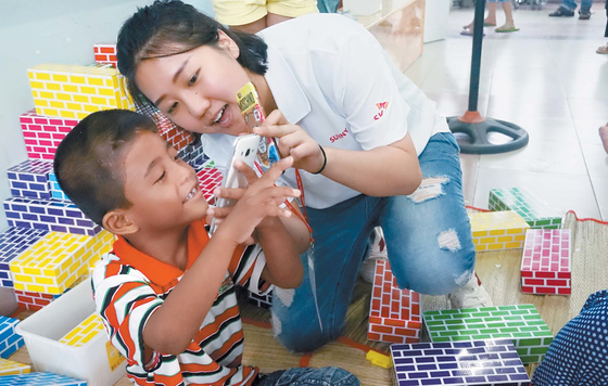 SK는 1996년부터 의료 혜택을 받기 어려운 지역에 사는 안면기형 장애 어린이 3800여 명에게 수술비를 전액 지원해왔다. 사진은 SK 대학생 자원봉사단원이 5일 베트남 호치민시 투득 병원에서 수술을 앞둔 아이의 긴장을 풀어주는 모습. [사진·SK]