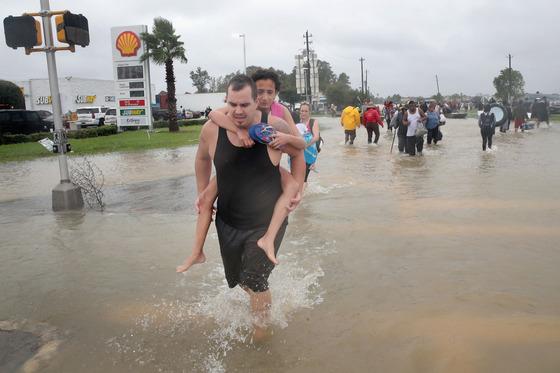 28일(현지시간) 미 텍사스 휴스턴 주민들이 허리케인 하비가 쏟아부은 비로 인해 잠긴 도심을 벗어나고 있다.[AFP=연합뉴스]