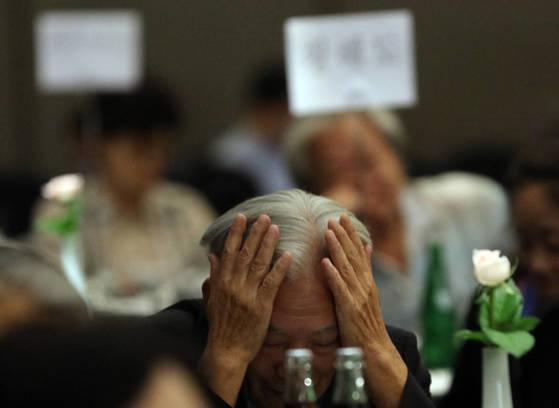 30일 서울AW컨벤션센터에서 열린 '2017 이산가족 초청행사'에서 한 참석자가 머리를 감싸고 있다. [연합뉴스]