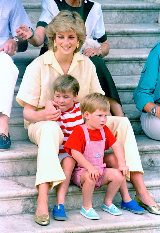 다이애나가 1987년 8월 스페인 마요르카섬에서 휴가를 보내면서 어린 윌리엄과 해리 왕자와 함께 왕궁 앞 계단에 앉아 있는 모습.[AP=연합뉴스]