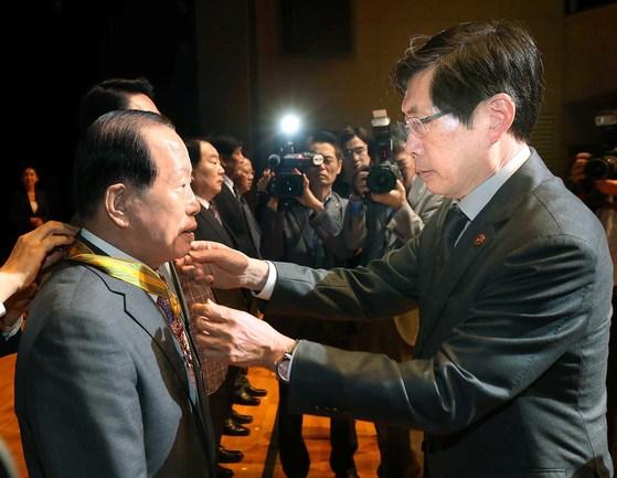 박상기 법무부 장관(오른쪽)이 31일 '2017 범죄예방 한마음대회'에서 조남길 전 동양임포트 회장에게 국민훈장 모란장을 수여하고 있다. [오종택 기자]